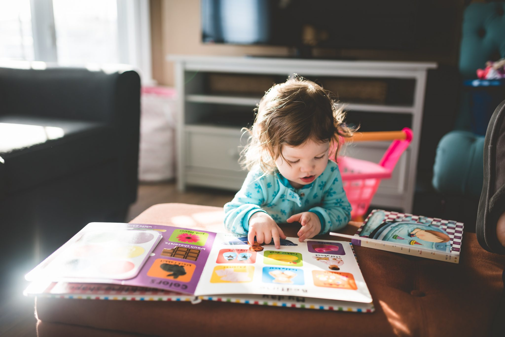 Preschool age girl reading a book and leaning on a coffee table