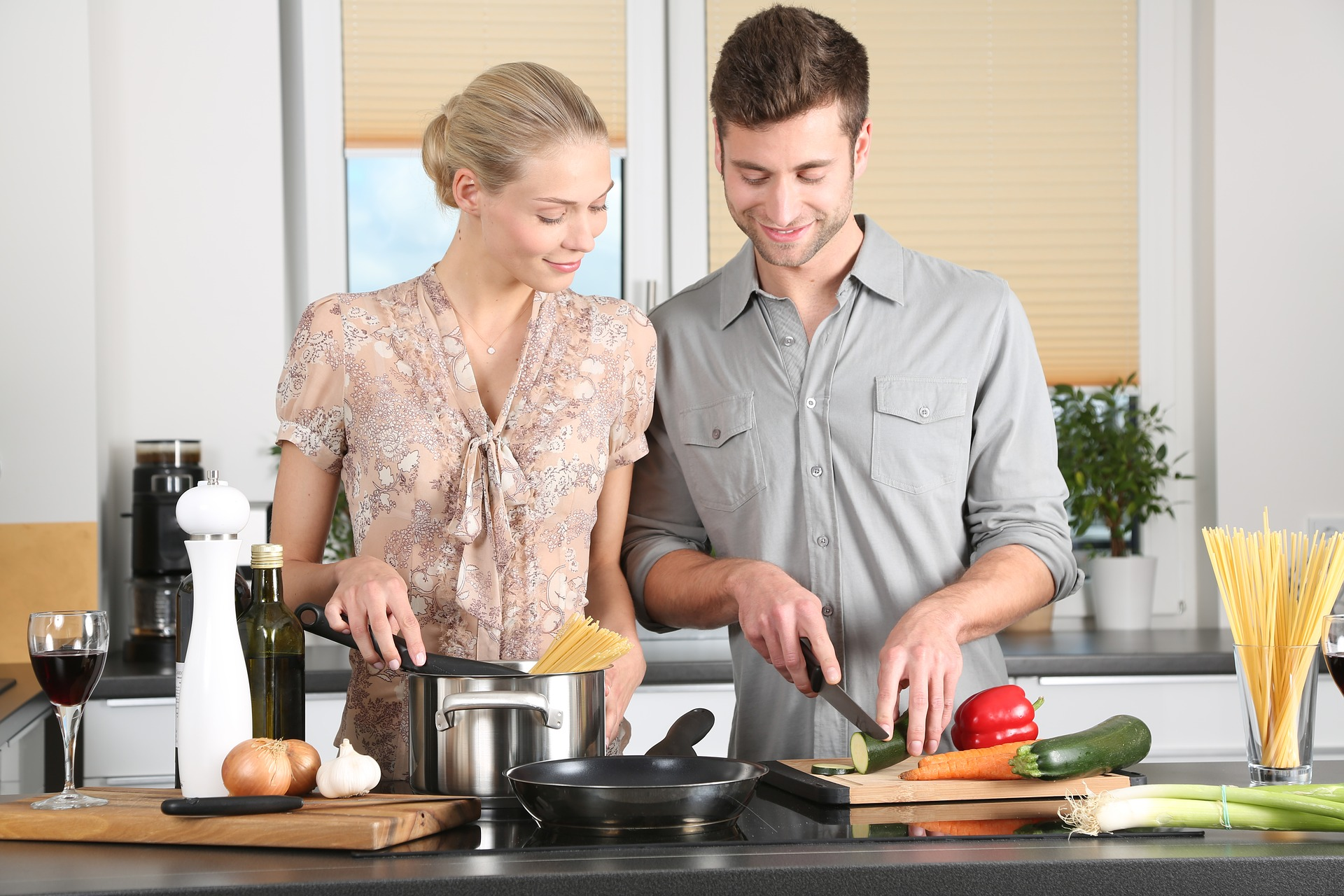 Man and woman preparing vegetables and pasta in the kitchen together smiling