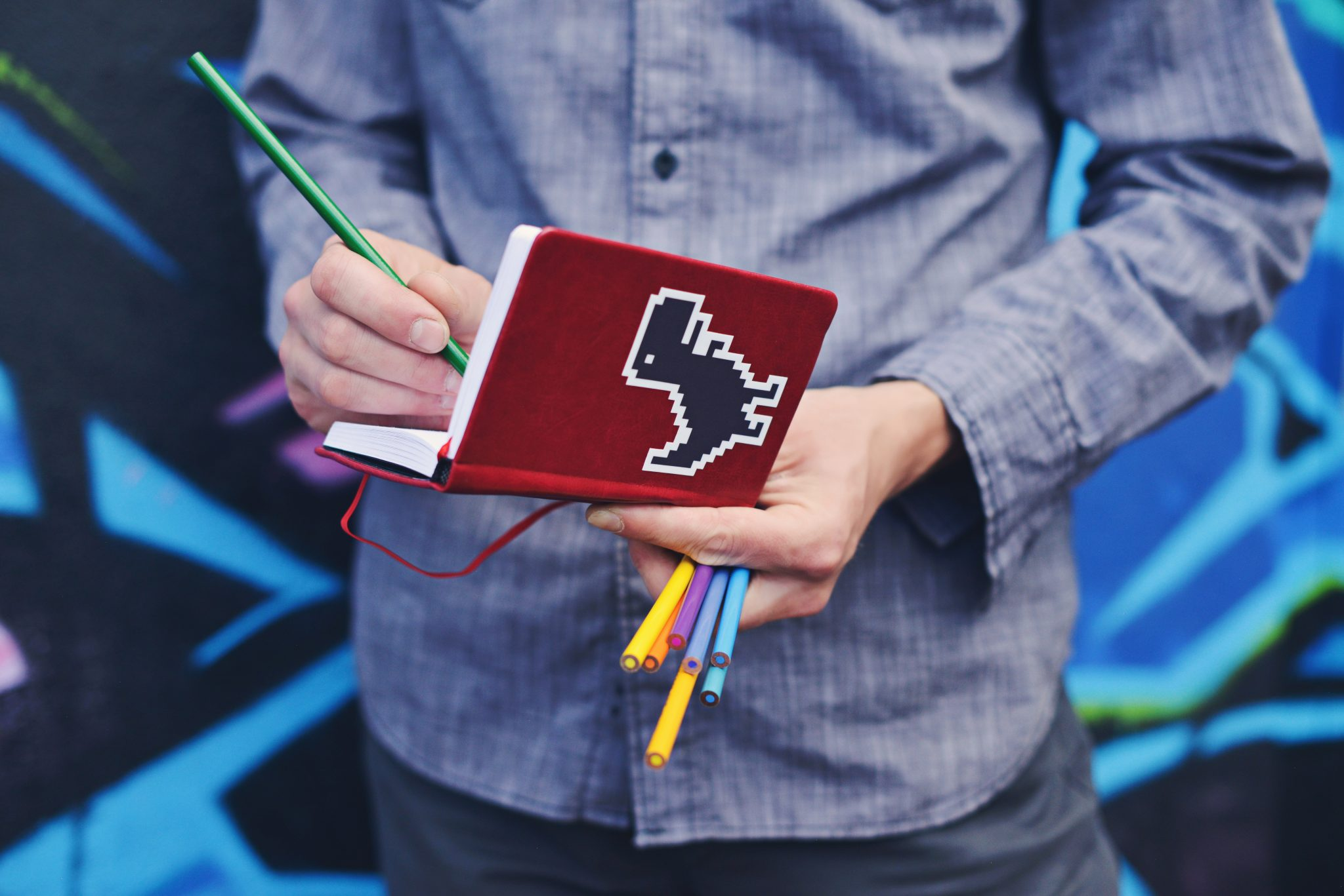 Man writing with a pencil in a red notebook with a dinosaur on it