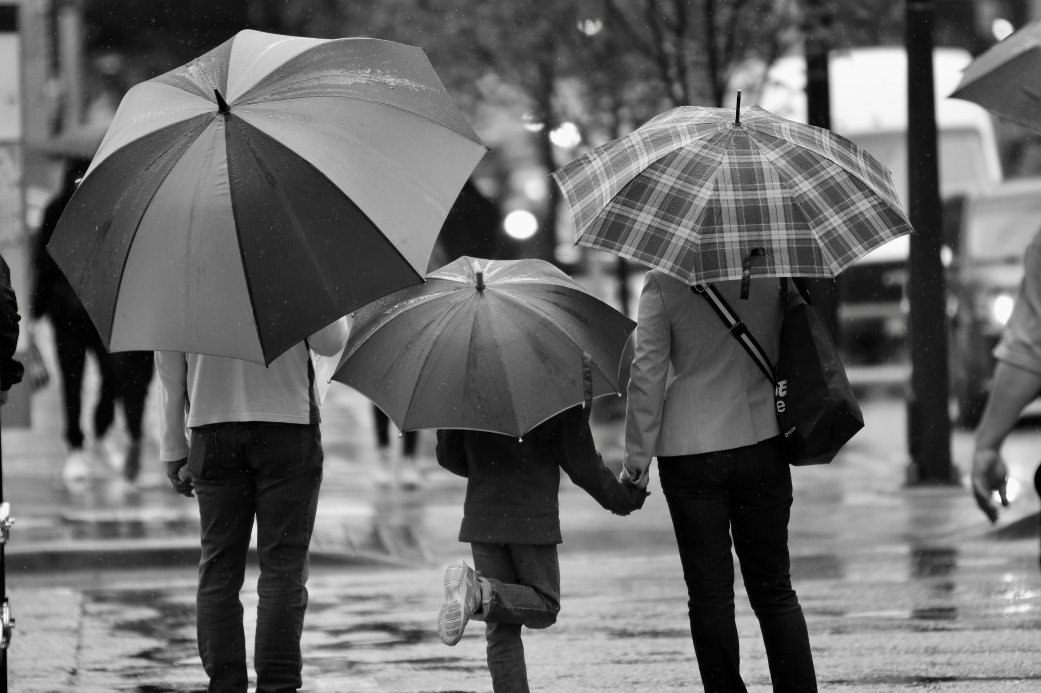 Black and white image of two parents holding hands with their child and holding umbrellas