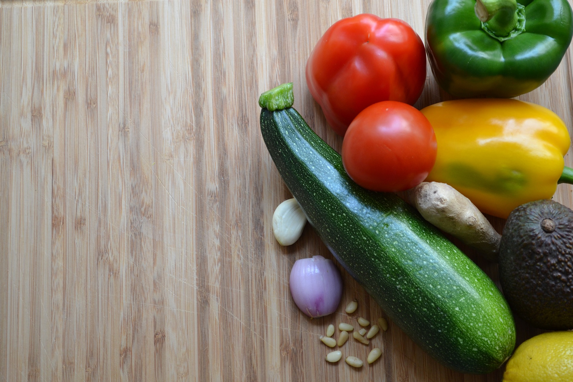 Zucchini, bell pepper, tomato, and onion arranged on a neutral background