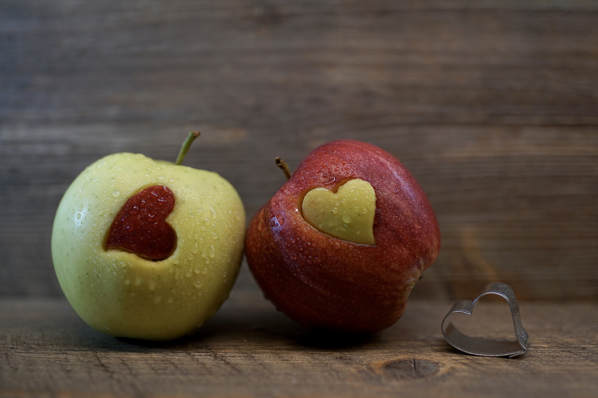 A red and green apple sitting on a wood table, each with a heart shape cut out of them