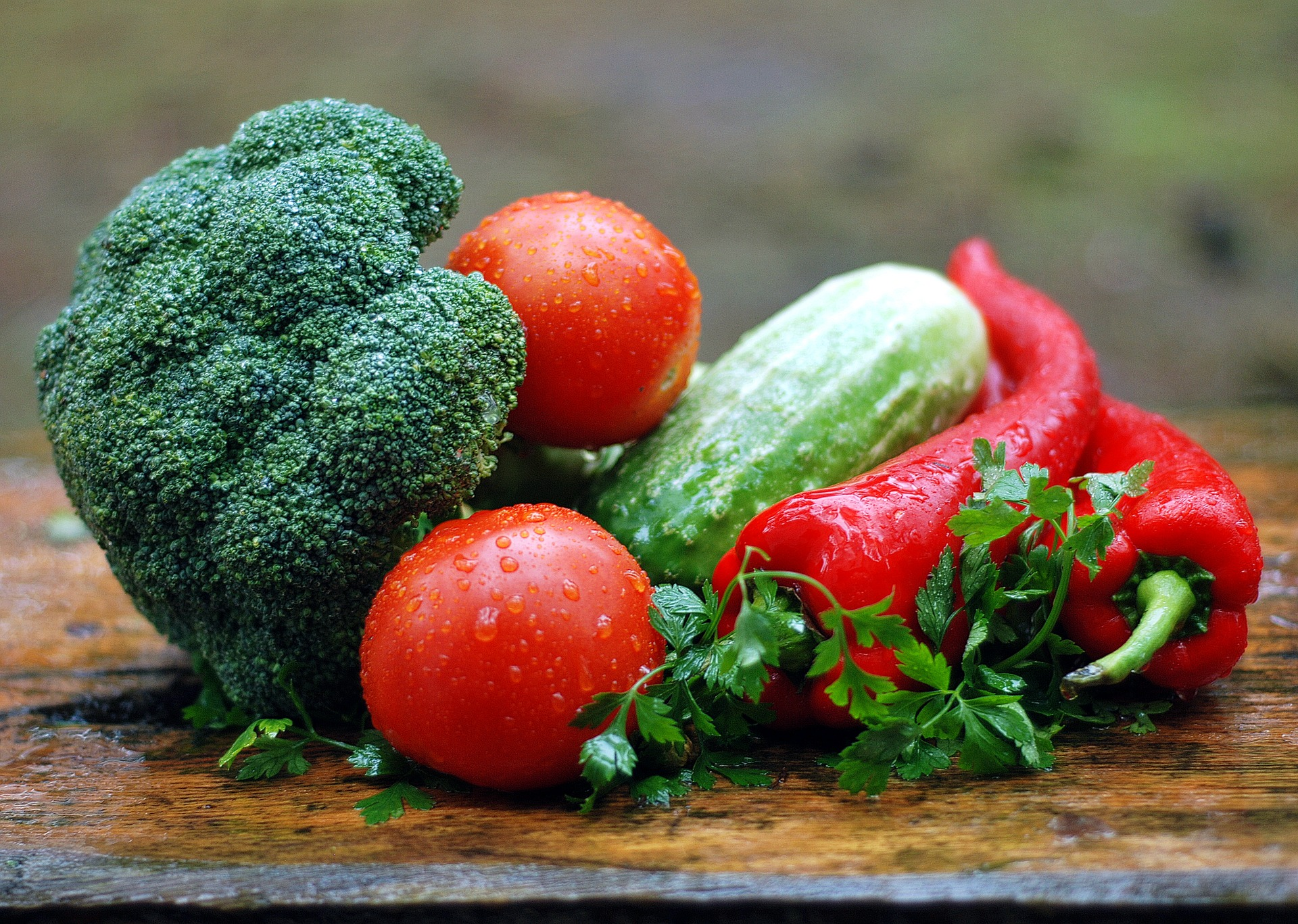 Broccoli, tomatoes, zucchini, and peppers piled on a wood surface