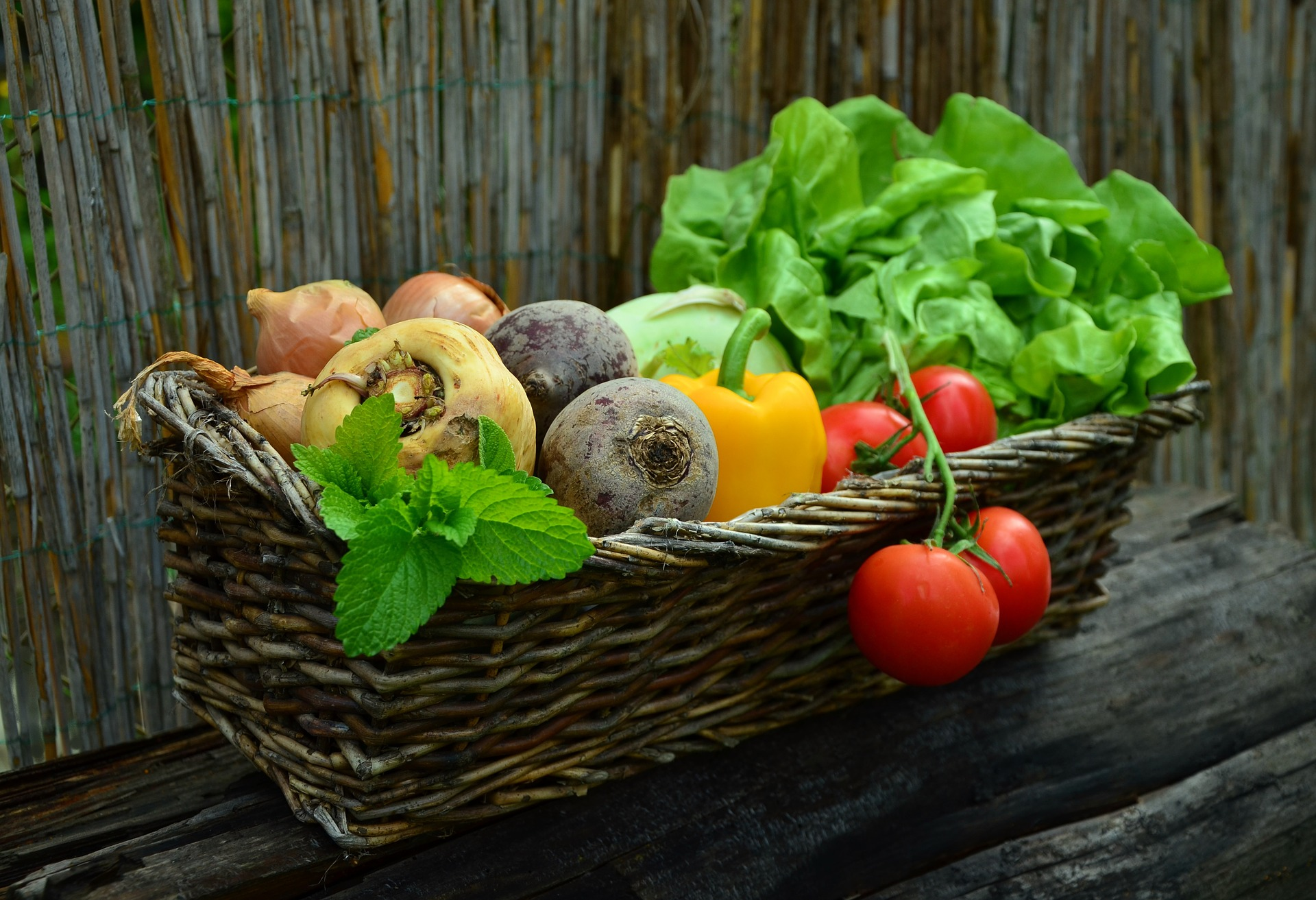 Colorful fresh vegetables in a wicker box with a wood background